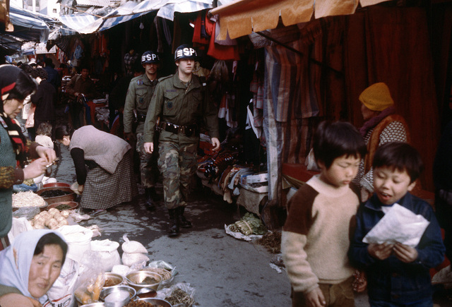 Security policemen patrol a market village at Son Tan Up during exercise Team Spirit '81