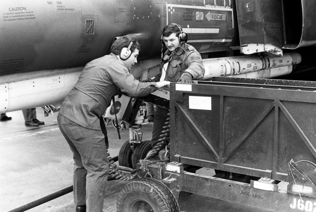 SGT Anderson and Loading Crew Supervisor, SSGT Ron Lowery, left to right, use a quick loader to load 20mm rounds into an F-4 Phantom II aircraft nose gun
