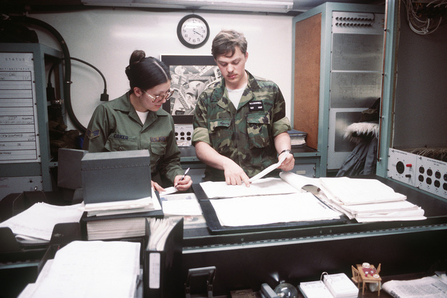 SRA Dorothy A. Coker and SGT Wayne C. Campbell go over computer run records. The airmen are the 621st Tactical Control Squadron members, involved in exercise Team Spirit '81