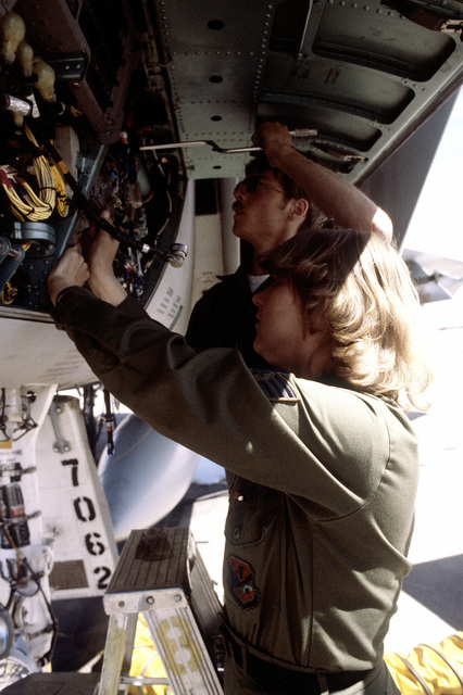 SSGT Karen Forsythe and AMN Steve Miles perform maintenance on a system of an F-15 Eagle aircraft during exercise Border Star '81
