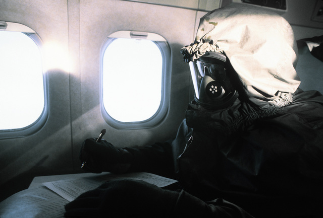 SSGT Lynn, wearing protective clothing, works on paperwork aboard a C-9A Nightingale aircraft en route to Ramstein Air Base, Germany. SGT Lynn is taking part in a chemical warfare training exercise