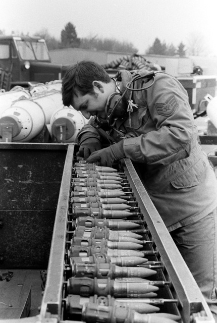 SSGT Ron Lowery checks a quick loader of 20mm rounds to ensure proper clipping. SSGT Lowery is a loading crew supervisor preparing to load the rounds into an F-4 Phantom II aircraft nose gun