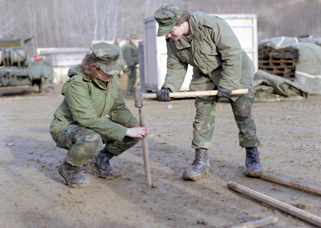 Two female Marines of Marine Aircraft Group 12 (MAG-12) do their share in helping to set up tents as exercise Team Spirit '81 gets underway