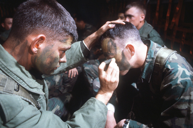 United States Marines aboard a C-141 Starlifter aircraft in flight, apply facial camouflage make-up for an assault mission during exercise Team Spirit '81