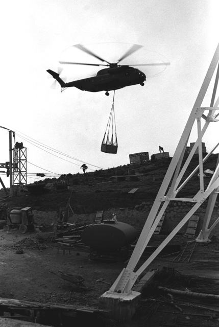 A Marine CH-53 Sea Stallion helicopter from Marine Medium Helicopter Squadron 165 (HMM-165) externally airlifts a crate to a staging area for equipment that will be used for the Sri Lanka television station. The airlift is a humanitarian gesture by the U.S. Marine Corps