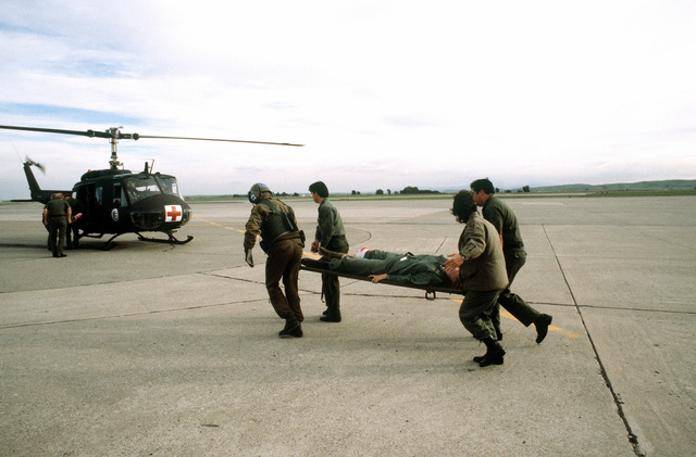 """Airmen carry a """"patient"""" to a UH-1N Iroquois helicopter during an aeromedical evacuation training exercise"""