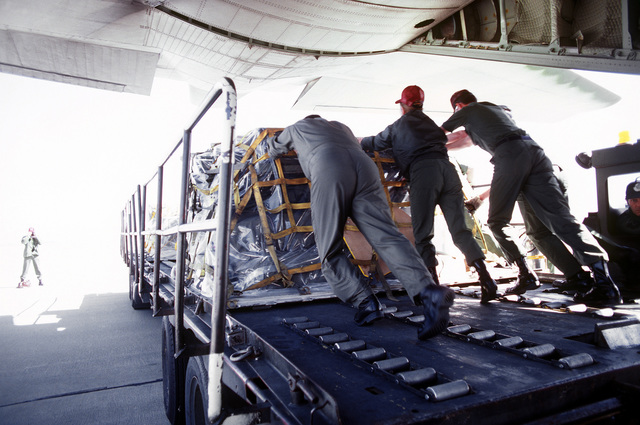 Members of the 32nd Aeromedical Evacuation Group unload a pallet of cargo from a C-130 Hercules aircraft onto a loader during an aeromedical evacuation training exercise