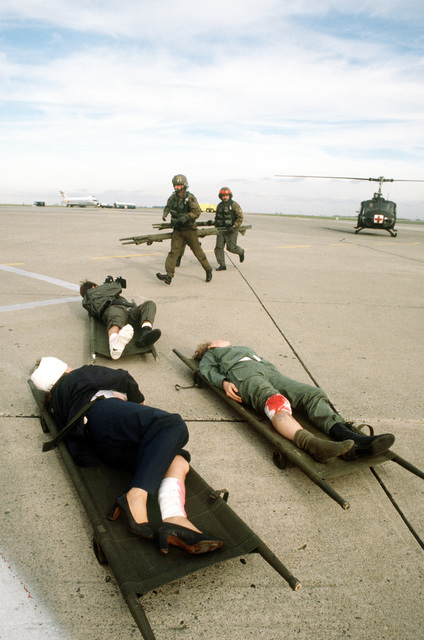 Patients wearing bandages lie on litters before being loaded aboard a UH-1N Iroquois helicopter during an aeromedical evacuation training exercise