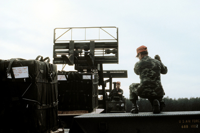 An airman directs a forklift operator to load a container delivery system airdrop cargo onto a tractor-trailer. The airmen are from the Air National Guard, involved in exercise Sentry Cowboy I