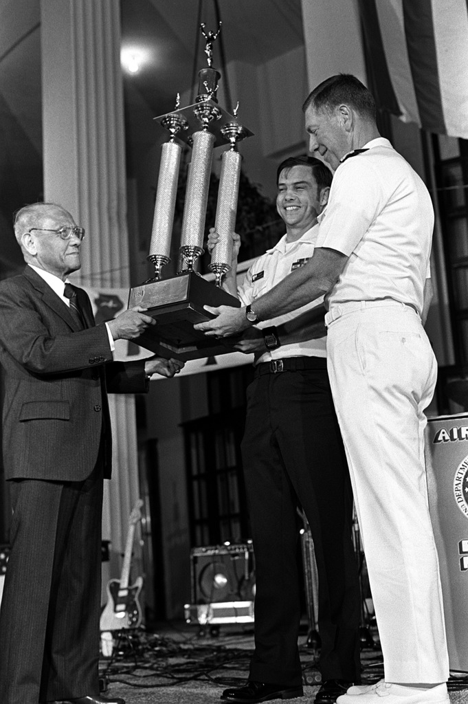 United Services Organization Director Salvador C. Pena presents the trophy for outstanding sailor in the Philippines to MASTER-at-Arms 1ST Class Larry Knapp. With MA1 Knapp is RADM Lee Levenson. The presentation is being made during the annual USO Six-Star Salute at the U.S. Embassy