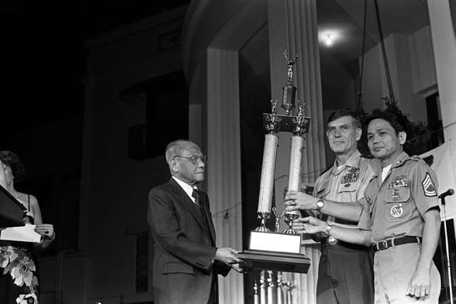 United Services Organization Director Salvador C. Pena presents the trophy for outstanding soldier in the Philippines to SFC Benigno Pineda. With Pineda is BGEN James Foss. The presentation is being made during the annual USO Six-Star Salute at the U.S. Embassy