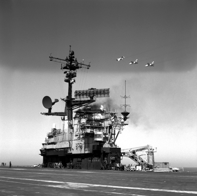 A close-up view of the island of the aircraft carrier USS CORAL SEA (CV-43) as three Attack Squadron 305 (VA-305) A-7B Corsair II aircraft fly in formation overhead. The CORAL SEA is taking part in carrier qualifications off the coast of southern California