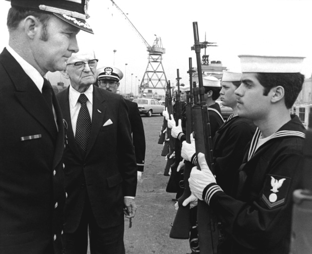 CDR Henry Strickland, front, and Sen. John C. Stennis, D-Mississippi, review the honor guard from the guided missile destroyer USS CHANDLER (DDG-995) prior to the ship's commissioning ceremony. Stennis is the principal speaker and Strickland will assume command of the CHANDLER during the ceremony