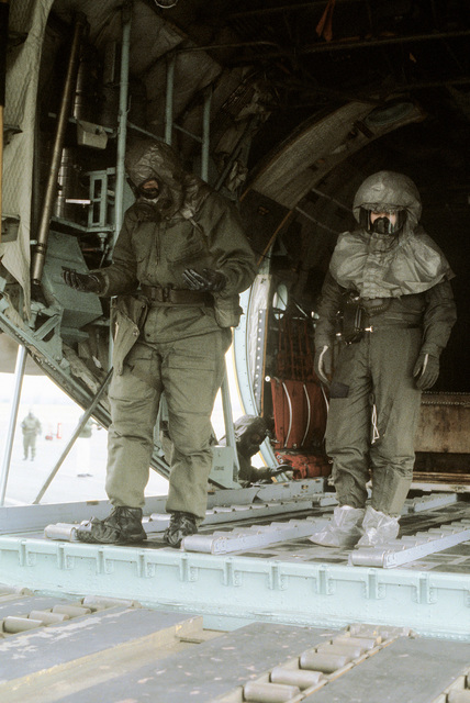 Airmen wearing protective clothing wait to load a cargo pallet aboard a C-130 Hercules aircraft during a chemical warfare exercise. The crew members are from the 317th Military Airlift Wing, Air National Guard
