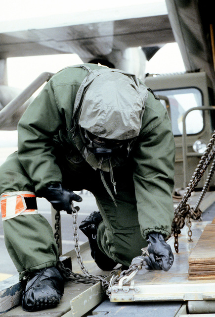 An airman wearing protective clothing secures a cargo pallet with chains before loading it aboard a C-130 Hercules aircraft. The airman is from the 317th Military Airlift Wing, Air National Guard, involved in a chemical warfare exercise
