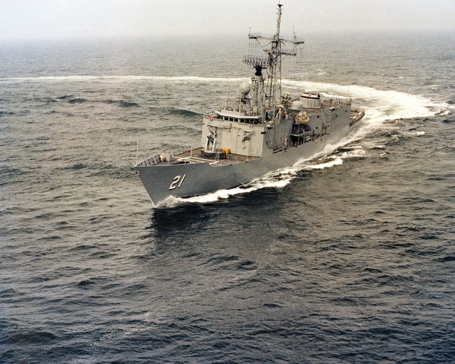 An aerial port bow view of the Oliver Hazard Perry class guided missile frigate USS FLATLEY (FFG 21) executing a starboard turn during her acceptance trials