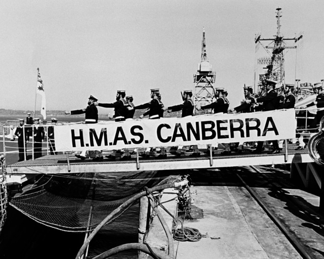 A Royal Australian Navy guard squad marches across the gangplank to go aboard the frigate HMAS CANBERRA (F-02), during the ship's commissioning ceremony at Todd Pacific Shipyards Corporation