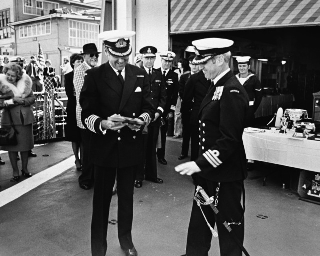 CAPT M. G. Hole, the son of the gunnery officer of the first HMAS CANBERRA, makes a presentation to CMDR B. Wilson, commanding officer of the current Australian frigate HMAS CANBERRA (F-02), during the ship's commissioning ceremony at Todd Pacific Shipyards Corporation