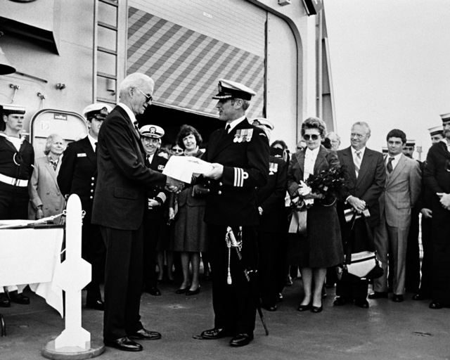Mr. Irvine, former commanding officer of the ex-USS CANBERRA, makes a presentation to CMDR B. Wilson, commanding officer of the Australian frigate USS CANBERRA (F-02), during the ship's commissioning ceremony at Todd Pacific Shipyards Corporation