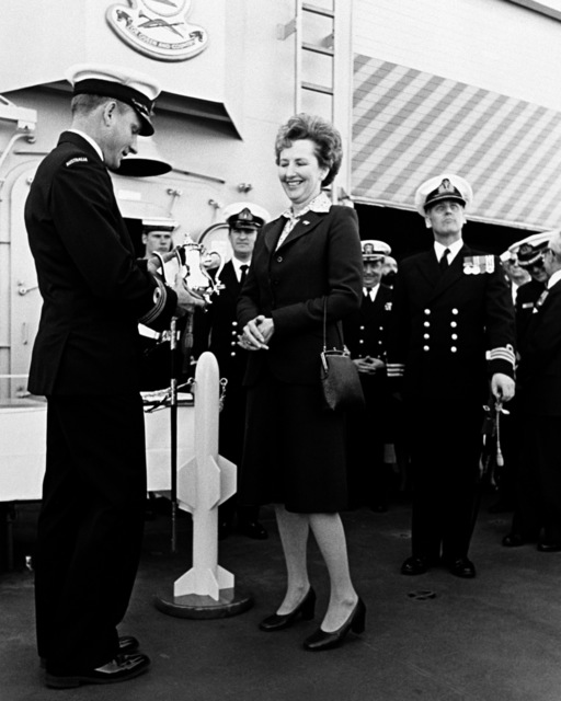 Mrs. O'Farrell makes a presentation to LCDR R. A. Christie, executive officer of the Australian frigate HMAS CANBERRA (F-02), during the ship's commissioning ceremony at Todd Pacific Shipyards Corporation. The presentation is on behalf of Lady Tange, the ship's sponsor