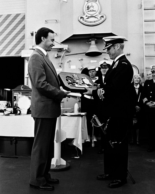 Peter Vallee makes a presentation to Commander B. Wilson, commanding officer of the Australian frigate HMAS CANBERRA (F-02), during the ship's commissioning ceremony at Todd Pacific Shipyards Corporation. The presentation is on behalf of the citizens of Canberra, the city for which the ship was named