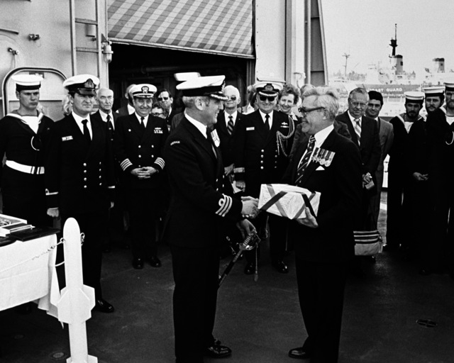 Sir Nicholas Parkinson makes a presentation to CMDR B. Wilson, commanding officer of the Australian frigate HMAS CANBERRA (F-02), during the ship's commissioning ceremony at Todd Pacific Shipyards Corporation