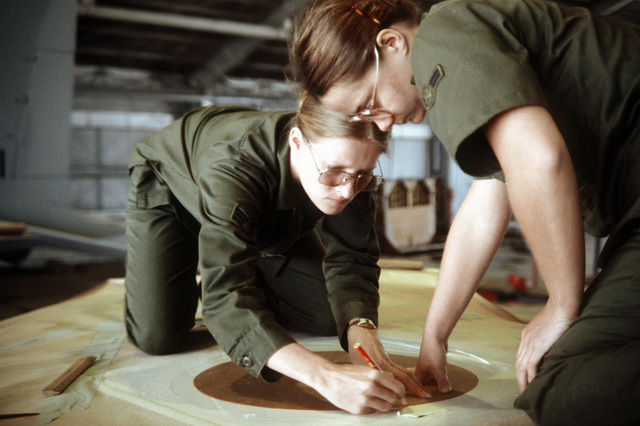 A1C Vickie M. Green assists SRA Louise M. Cortez in masking an area on a Japanese Air Self Defense Force F-15 Eagle aircraft wing