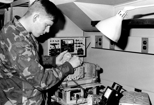 CPL Scott Marchall, a communications technician with Marine Air Traffic Control Squadron 18, Detachment A, troubleshoots an aircraft radio transmitter