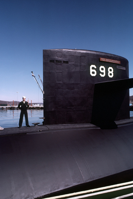 A crewman stands at parade rest aboard the nuclear-powered attack submarine USS BREMERTON (SSN-698) during commissioning ceremonies