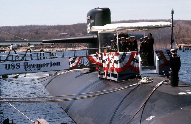 A starboard bow view of the nuclear-powered attack submarine USS BREMERTON (SSN-698) with distinguished guest on the speakers platform during commissioning ceremonies