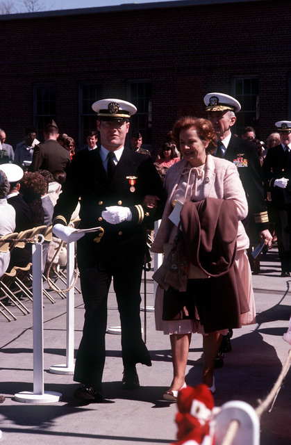 An officer escorts a guest to her seat prior to commissioning ceremonies for the nuclear-powered attack submarine USS BREMERTON (SSN-698)