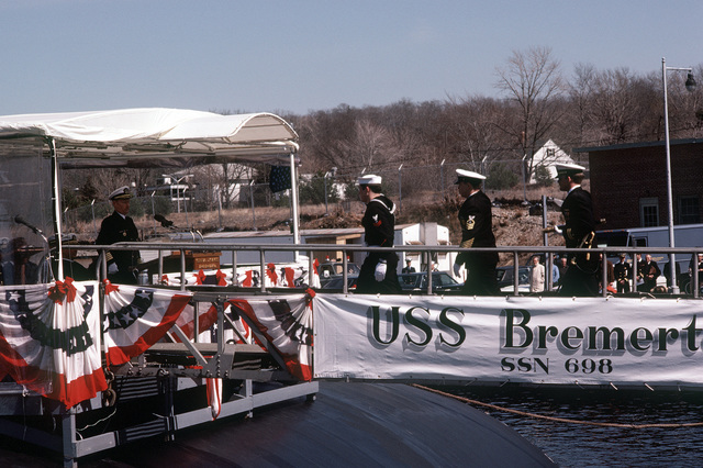 Crewmen salute as they are piped aboard the nuclear-powered attack submarine USS BREMERTON (SSN-698) during commissioning ceremonies