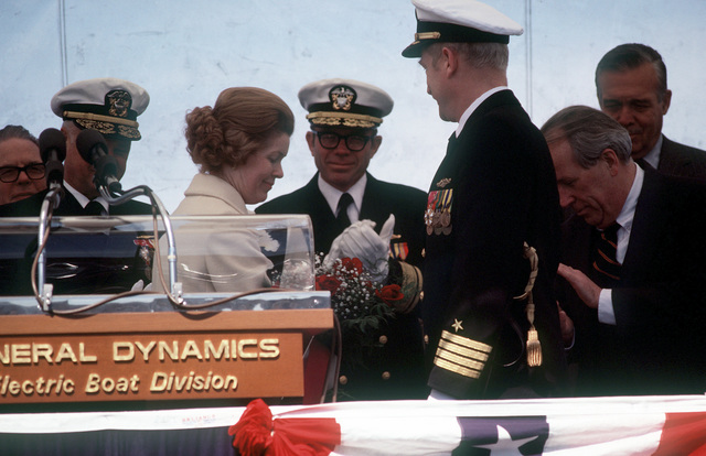 Mrs. Henry Jackson receives flowers from CAPT Thomas H. Anderson, commanding officer of the nuclear-powered attack submarine USS BREMERTON (SSN-698), during the ship's commissioning ceremonies