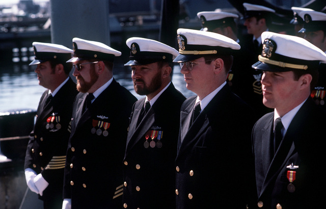 Officers and crew from the nuclear-powered attack submarine USS BREMERTON (SSN-698) stand in formation during commissioning ceremonies