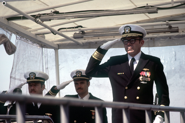 RADM Carl A. Brettschneider salutes during commissioning ceremonies for the nuclear-powered attack submarine USS BREMERTON (SSN-698)