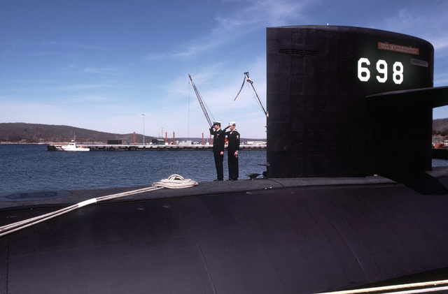 Two crewmen salute after colors are raised aboard the nuclear-powered attack submarine USS BREMERTON (SSN-698) during commissioning ceremonies