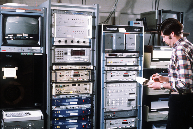 A technician, doing a weather physics experiment, collects cloud data from a computer panel for directing Air Force aircraft at the Man Computer Interactive Data Acquisition System (MCIDAS) section, Air Force Geophysics Laboratory (AFGL)