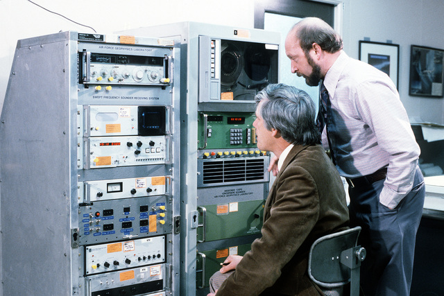 Dr. James A. Whalen, physicist, and Dr. Jurgen Buchau, left to right, discuss the operation of the SWEPT frequency sounder receiving system in the Auroral Ionospheric Research Room of the Air Force Geophysics Laboratory (AFGL)