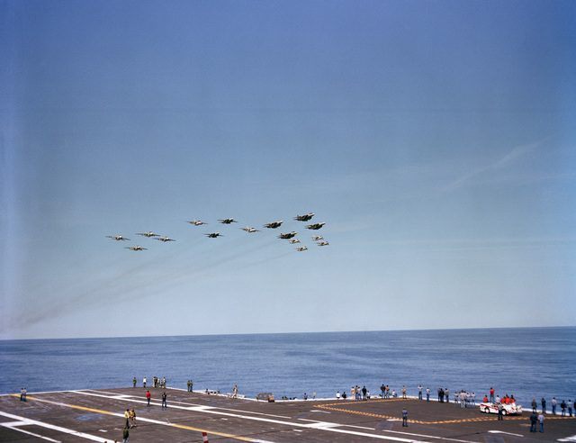 Aircraft from Carrier Air Wing Eight (CVW-8) fly over the nuclear-powered aircraft carrier USS NIMITZ (CVN 68) during an air show. The aircraft include (right to left) F-14 Tomcats (top right), A-7 Corsair IIs (bottom right), S-3 Viking and A-6 Intruders