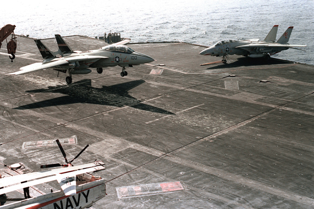 An overhead right front view of an F-14A Tomcat from Fighter Squadron 51 (VF-51) landing on the flight deck of the aircraft carrier USS KITTY HAWK (CV-63)
