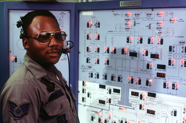 SSGT Thomas stands at the control panel for the satellite thruster facility, at the Rocket Propulsion Lab