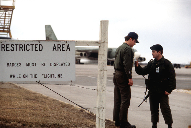 STAFF Sergeant Kevin Goatley of the 321st Security Police Squadron inspects the security badge of AIRMAN 1ST Class Mark Van Bergh at the gate to the B-52 Stratofortress aircraft flight line. Bergh is an environmental systems specialist from the 319th Field Maintenance Squadron