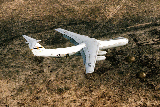 AN air-to-air right side view of a C-141B Starlifter aircraft dropping 82nd Airborne Division troops over Drop Zone B-70 during Dragon Team, the largest non-Joint Chiefs of STAFF airdrop training exercise in history. The aircraft is assigned to the 437th Military Airlift Wing