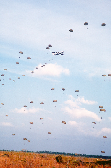 Parachutes dot the sky as paratroopers jump from a C-141B Starlifter aircraft during exercise Dragon Team, the largest non-Joint Chiefs of STAFF airdrop exercise in history taking place at Drop Zone B-70