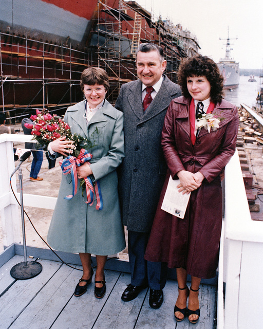 Miriam Groves Landry, left, sponsor's proxy; John Sullivan, president of Bath Iron works; and Susan Groves Mills, matron of honor, stand with their backs to the Oliver Hazard Perry class guided missile frigate USS STEPHEN W. GROVES (FFG 29). The GROVES has just slid down the ways at the conclusion of the launch ceremony
