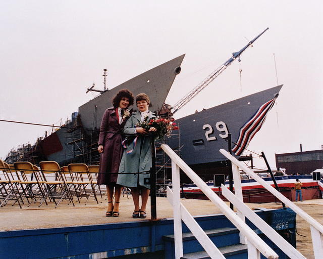 Susan Groves Mills, left, matron of honor and Miriam Groves Landry, sponsor's proxy, stand on the speakers platform prior to the launching ceremony for the guided missile frigate USS STEPHEN W. GROVES (FFG 29), background