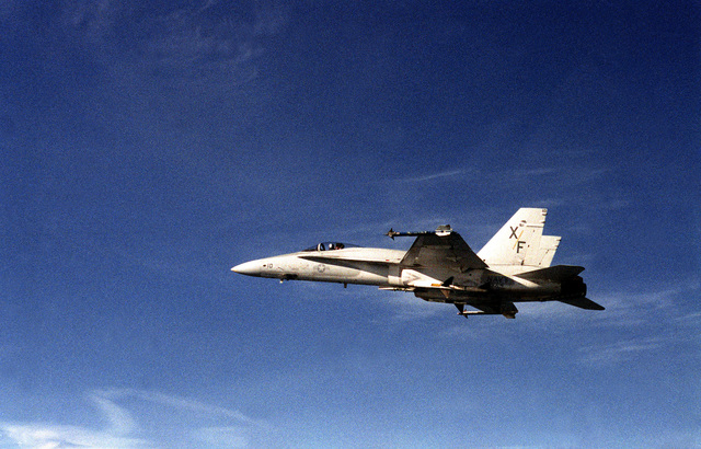 An air-to-air left side view of an F-18A Hornet aircraft with AIM-9L Sidewinder dummy missiles mounted on its wing tips. The aircraft is from Air Test and Evaluation Squadron 4 (VX-4) assigned to Fighter/AEW Wing Pacific