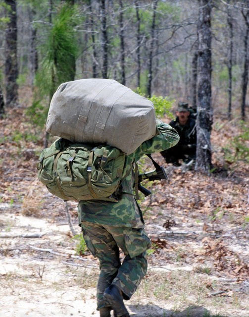 Combat Control Team member, MSGT James Charvat from the First Special Operations Wing, carries his HALO (High Altitude Low Opening) parachute into the woods