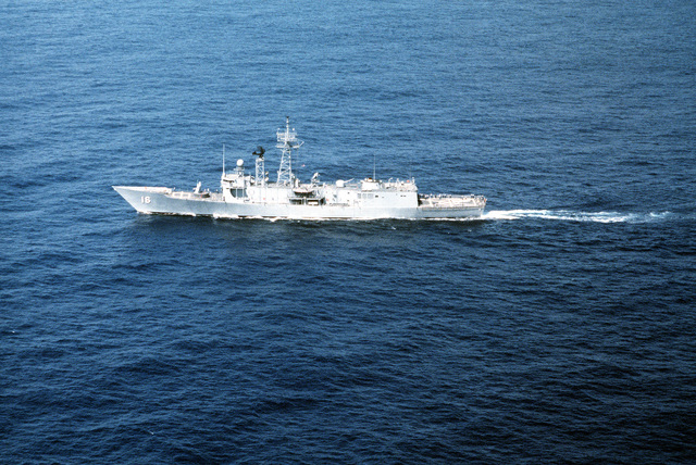 Aerial port beam view of the guided missile frigate USS CLIFTON SPRAGUE (FFG-16), which is being used as a target for F-105 Delta Dart aircraft, during exercise Gangbuster XI