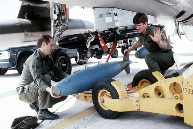 Airmen, with the aid of an MJ-1 bomb loader, load a 500-lb. Mark 82 bomb on an F-105 Delta Dart aircraft during exercise Gangbuster XI. The airmen are members of the 128th Tactical Fighter Squadron, 116th Tactical Fighter Wing, Texas Air National Guard